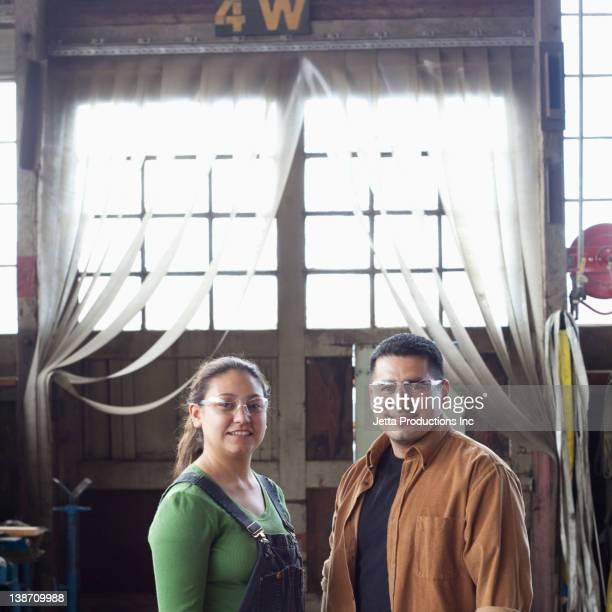 Hispanic workers standing in warehouse