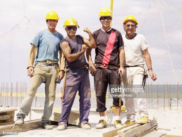 hispanic workers standing on construction site - vier personen stock-fotos und bilder