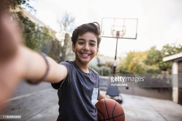 hispanic young boy taking a selfie and holding a basketball in his hands - drive ball sports stock pictures, royalty-free photos & images