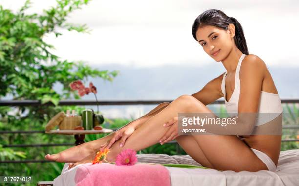 hispanic young woman applying moisturizing lotion onto her legs - knickers stock pictures, royalty-free photos & images
