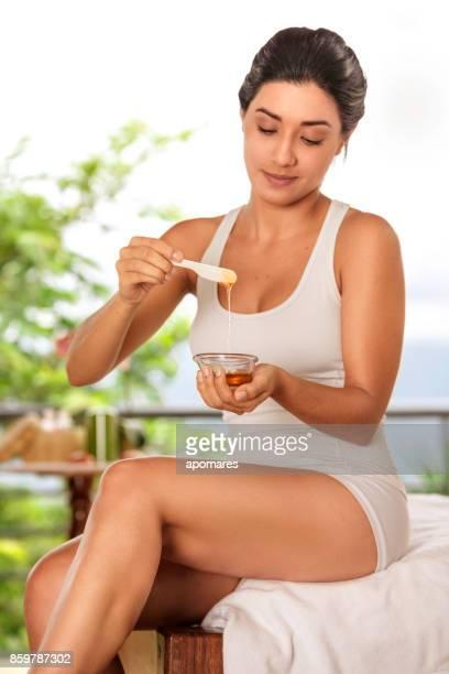 Hisoire jeune femme s'apprête à utiliser la cire d'épilation sur ses jambes