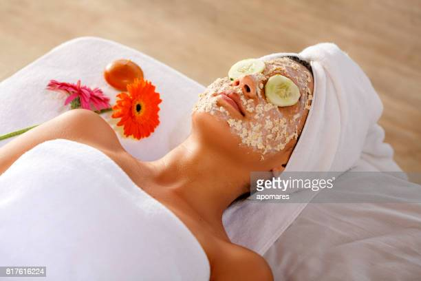 hispanic young woman laying on bed and getting oatmeal face scrub and resting with cucumber slices on eyes. - oatmeal stock pictures, royalty-free photos & images