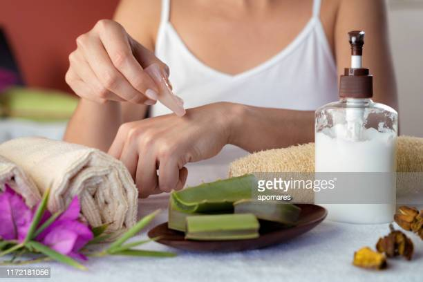 hispanic young woman moisturizing hands with aloe vera natural gel - aloe stock pictures, royalty-free photos & images