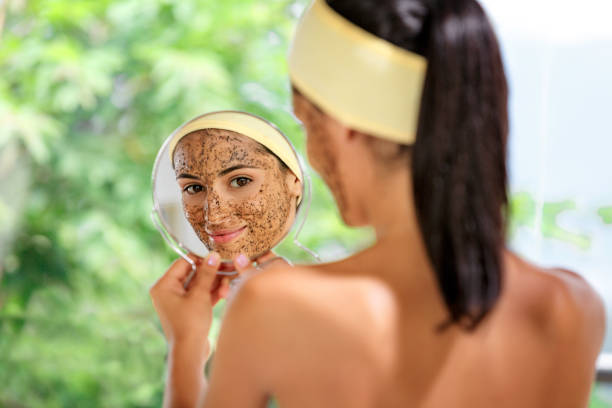 hispanic young woman with coffe face scrub after bath looking at herself on hand mirror. skin exfoliation. - exfoliation stock pictures, royalty-free photos & images