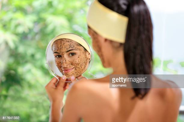 Hispanic young woman with coffe face scrub after bath looking at herself on hand mirror. Skin Exfoliation.