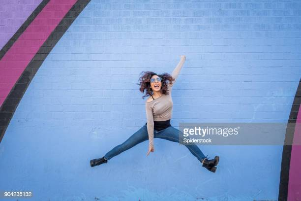 hispanic young woman with positive attitude - jumping stock pictures, royalty-free photos & images