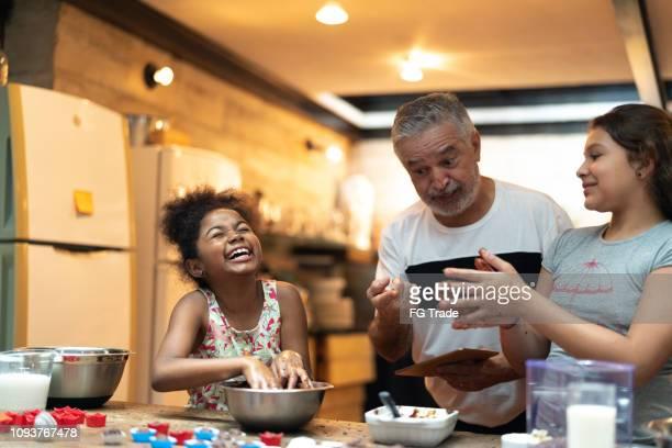 hispano-latino avô ensinar o neto a cozinhar em casa - eles estão preparando o brigadeiro brasileiro - cozinhando - fotografias e filmes do acervo