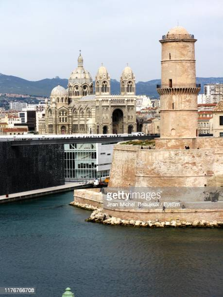 historic building by river against sky in city - marseille stock pictures, royalty-free photos & images