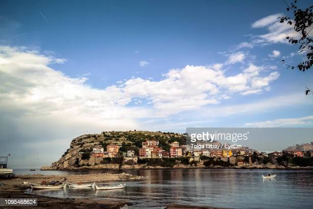 historic building by sea against sky in city - tolga erbay stock photos and pictures
