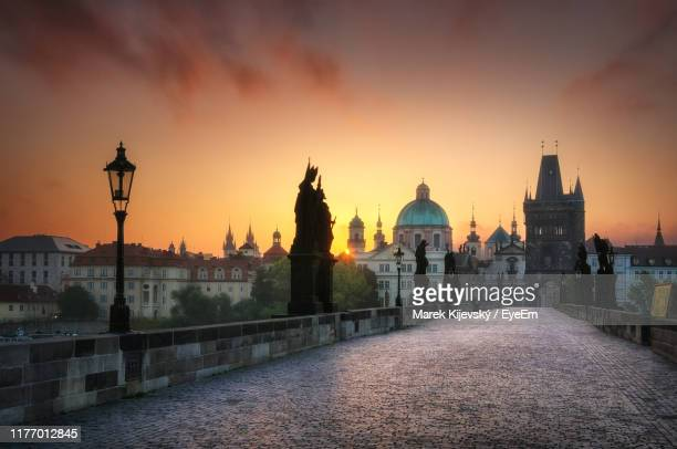 historic buildings against cloudy sky during sunset - charles bridge stock pictures, royalty-free photos & images