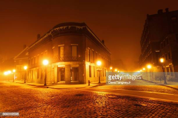 historic cobblestone streets in lowell on a foggy night - lowell massachusetts stock pictures, royalty-free photos & images