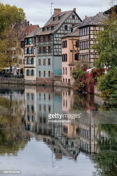 Historic houses and reflections on a canal in petite France quarter.