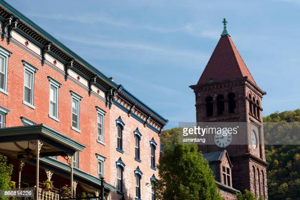 historic inn at jim thorpe and clock tower of carbon county courthouse - jim thorpe pennsylvania stock photos and pictures