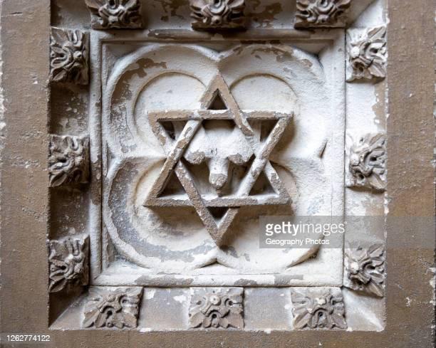 Historic interior of East Bergholt church, Suffolk, England, UK baptismal font stonework detail Star of David.
