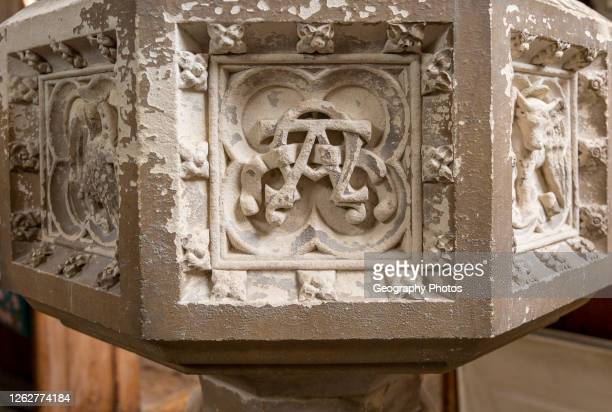 Historic interior of East Bergholt church, Suffolk, England, UK baptismal font stonework detail alpha omega symbol.