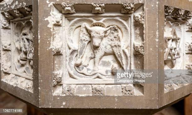 Historic interior of East Bergholt church, Suffolk, England, UK baptismal font stonework detail.