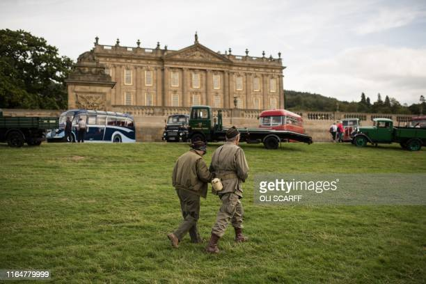 Historic military reenactors walk past vintage vehicles on display in front of Chatsworth House on the first day of the Chatsworth Country Fair in...