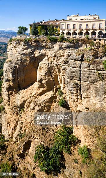 Historic National Parador hotel building perched on sheer cliff top in Ronda Spain