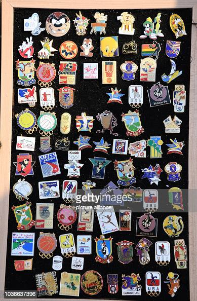 Historic Olympics pins are displayed on the board of a pin collector