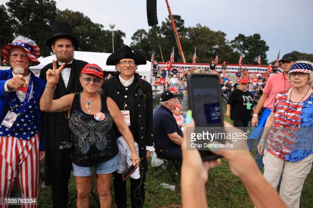 """Historic re-enactors and a man playing the part of Uncle Sam pose for photographs with supporters of former President Donald Trump during a """"Save..."""