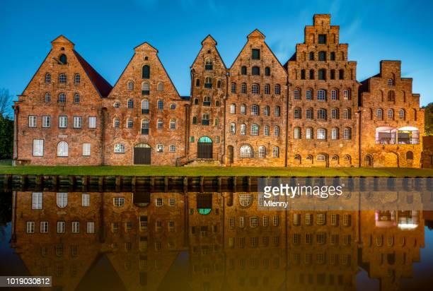 historische zout storehouses lübeck bakstenen gebouwen trave rivier bij nacht lubeck, duitsland - sleeswijk holstein stockfoto's en -beelden