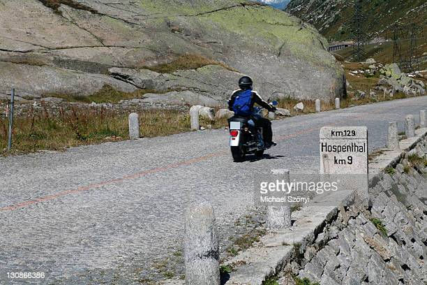 Historic section of cobblestone pavement on the old Gotthard pass route with milestone to Hospental and old motorbike, Gotthard, Switzerland