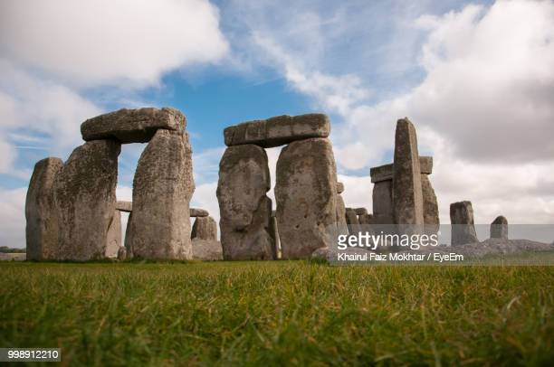 historic stonehenge on field against sky - ancient history stock pictures, royalty-free photos & images
