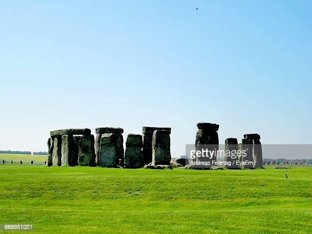 Historic Stonehenge On Grass Against Blue Sky