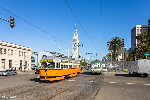 historic tramway on the embarcadero along san francisco waterfront in california - tram stock photos and pictures