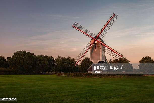 A historic windmill at sunset with a bench
