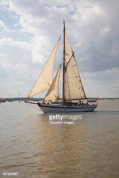 Historic wooden sailing yacht boat in full sail at the mouth of River Deben Suffolk England