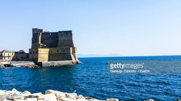 historical building by sea against clear blue sky - lookout tower stock pictures, royalty-free photos & images