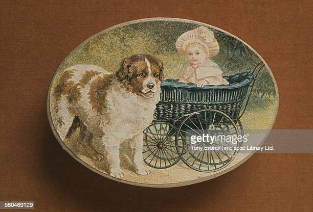 A historical Cadbury chocolate box featuring a painting of a child in a pram with a dog circa 1970