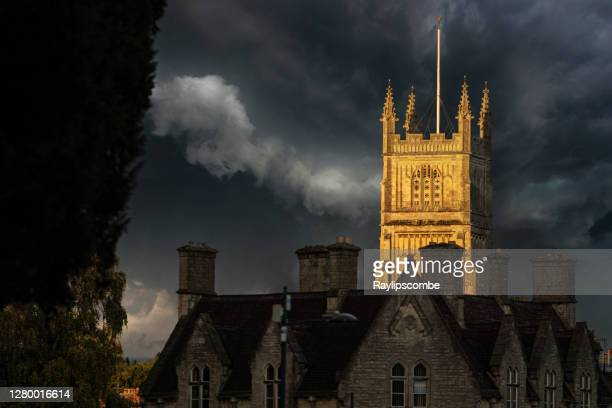 historical cirencester parish church of st john the baptist in the cotswolds, bathed in a shaft of late evening sunshine against a stormy brooding sky in early autumn. - anglican stock pictures, royalty-free photos & images