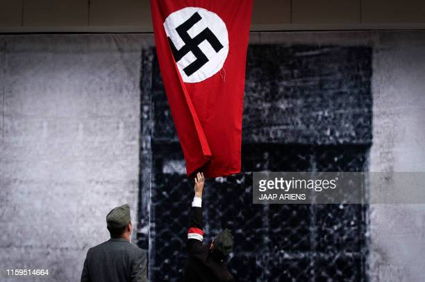 Historical re-enactment enthusiast dressed up as a Polish resistance fighter performs in front of a mock Nazi flag on August 3, 2019 in Warsaw during...