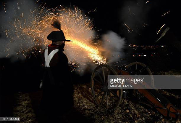 Historical re-enactment enthusiasts dressed as soldiers fire a cannon in front of the Peace Memorial on Prace hill on December 2, 2016 on the eve of...
