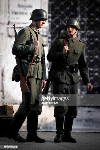 Historical re-enactment enthusiasts dressed up as Nazi soldiers talk on August 3, 2019 in Warsaw before performing in the re-enactement of the WWII...