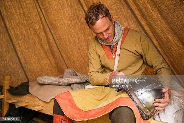 A historical reenactor in the Norman Camp polishes his helmet before a reenactment of the Battle of Hastings on October 15 2016 in Battle England...