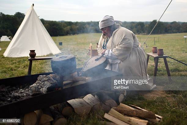 A historical reenactor uses a bellows to start a camp fire ahead of a reenactment of the Battle of Hastings on October 14 2016 in Battle England...