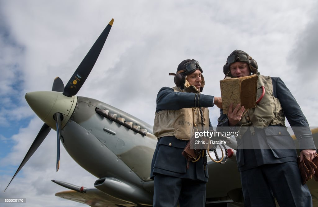 Historical reenactors and pilots Nigel Carver (L) and George Bruckert (R) pose for photographs next to a Spitfire at the Biggin Hill Festival of Flight on August 19, 2017 in Biggin Hill, England. The Biggin Hill Festival of Flight is an annual airshow event and in 2017 the airport is celebrating its centenary. The airport only became exclusively business and general aviation in 1959, prior to which it was used by the British Royal Air Force.