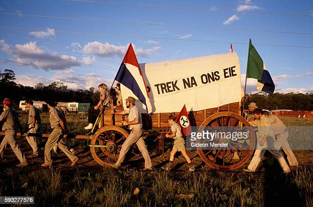 Historical reenactors participate in a reenactment of the Great Trek in South Africa Flags of the Afrikaner Resistance Movement and Transvaal are...