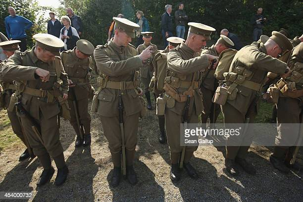 Historical society members dressed in uniforms to represent World War I British soldiers of the Middlesex Regiment put away their bayonets at a...
