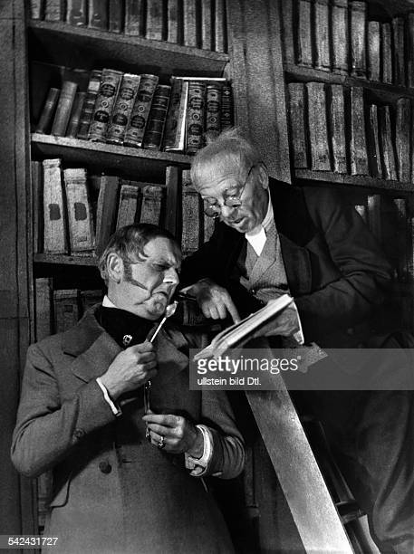 Historizing quotation of the bookworm motif by Carl Spitzweg two older men in costumes in front of a bookshelf in a library Photographer Charlotte...