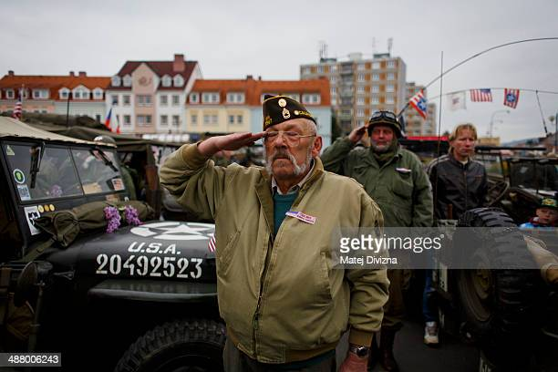 History enthusiasts dressed in WWII US Army uniform salute during U S anthem during stop over the 'Convoy of Liberation' event which drive through...