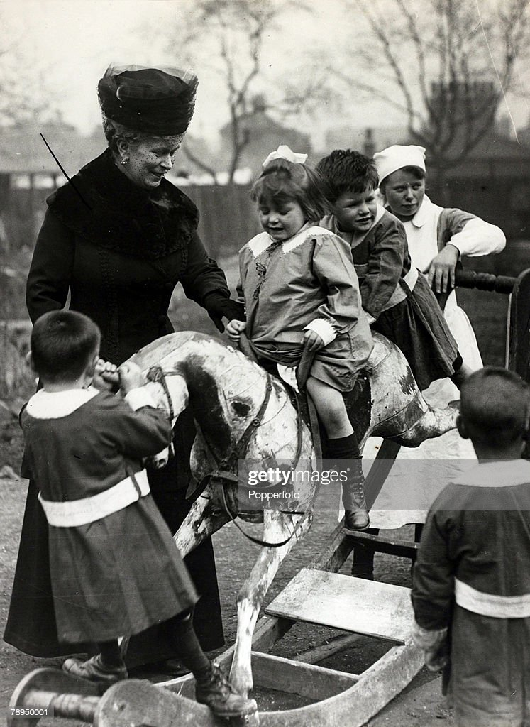 History Personalities. British Royalty. pic: 1919. HM.Queen Mary pictured in this happy picture at Deptford, London, at a day nursery, with children on a rocking horse. Queen Mary (1867-1953) born Mary of Teck, became Queen Consort when her husband King G : News Photo