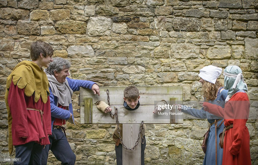 History student in stocks, Bolton Castle, a 14th century Grade 1 listed building and Scheduled Ancient Monument : Stock Photo