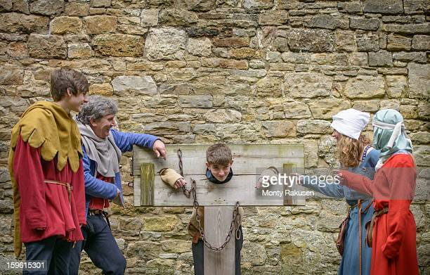 history student in stocks, bolton castle, a 14th century grade 1 listed building and scheduled ancient monument - historical reenactment stock photos and pictures