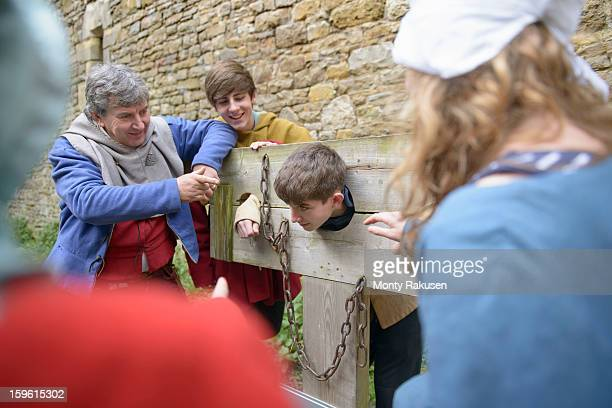 history student in stocks, bolton castle, a 14th century grade 1 listed building and scheduled ancient monument - punishment stocks stock pictures, royalty-free photos & images