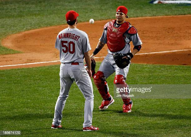 A hit by Stephen Drew of the Boston Red Sox falls between Adam Wainwright and Yadier Molina of the St Louis Cardinals in the second inning of Game...
