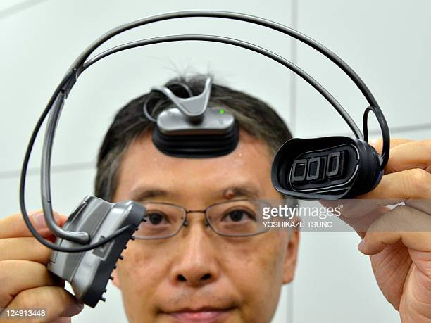 Hitachi engineer Takeshi Ogino dispays a portable 'brain-machine' interface' equipped with an optical sensor in a headset to measure prefrontal...